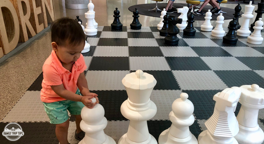 child playing with chess pieces at austin central library